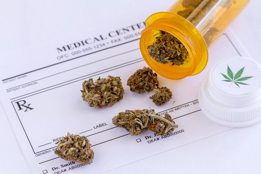 Medical marijuana buds spilling out of prescription bottle with lid onto blank medical prescription pad